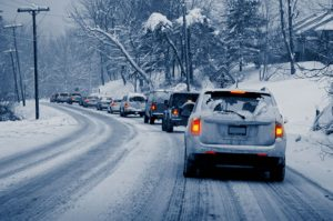 A lineup of cars drive on a snowy roadway