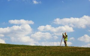 A surveyor stands alone in a grassy field