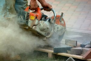 A man cuts tiles with a circular saw and creates a cloud of dust
