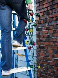 A person holds a string of Christmas lights while standing on a ladder