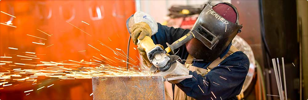 A woman uses a power grinding tool while wearing a welding helmet as sparks fly