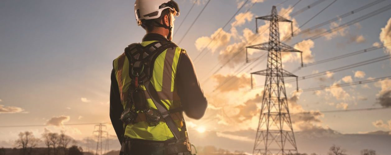 Man wearing harness and looking into sunset with hydro lines in the background