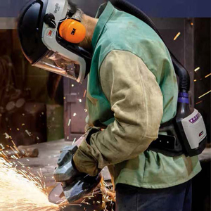 A man welding while wearing a PAPR.