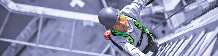 Construction worker wearing a harness is climbing a tower.