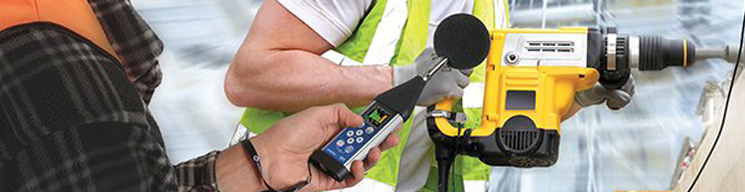 Worker holding a noise dosimeter to measure noise levels.