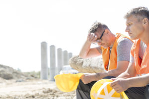Tired supervisor sitting with colleague at construction site wipes sweat from his brow
