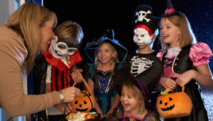 Trick or treaters gather for candy at a woman's house