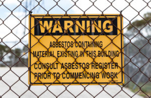 A warning sign posted to a fence warns anyone entering the construction site about the possibility of coming into contact with hazardous materials like asbestos.