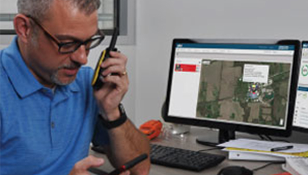 Man speaking into a walkie talkie with inet now on a computer in the background