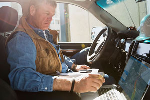 man sitting in truck using laptop to track plume modeling
