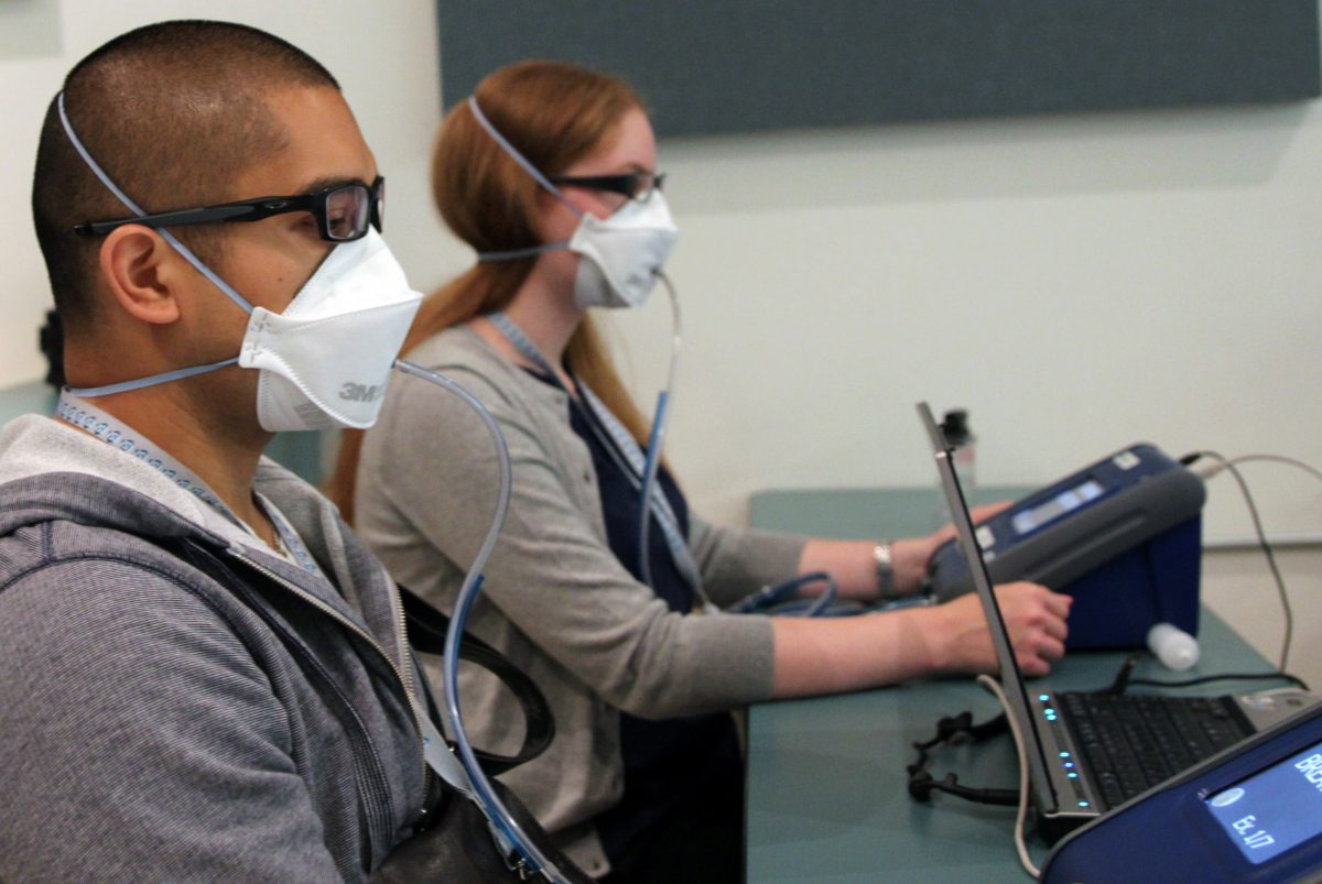 man and woman wearing masks and getting fit tested