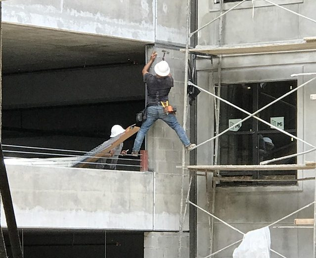 man standing between building and scaffolding