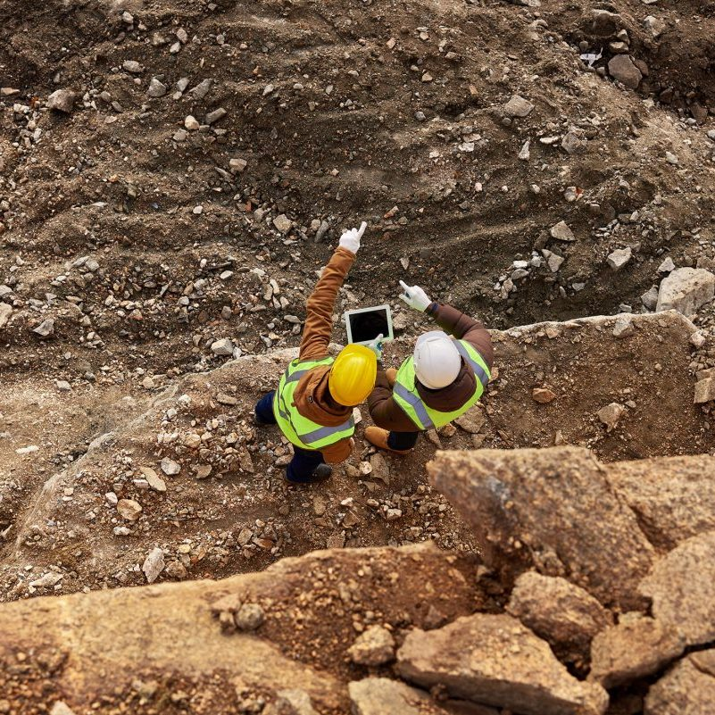 Two industrial workers wearing reflective jackets standing on mining worksite outdoors using digital tablet
