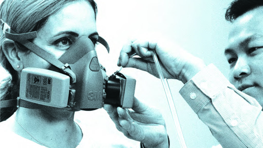 man placing hose on woman's respirator for her fit test