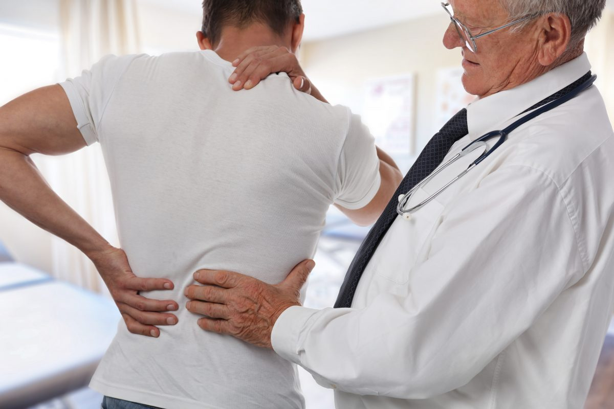 doctor feeling a man's lower back to find pain points