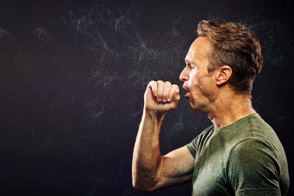 Side Profile Portrait against a Dark Background of a Caucasian adult man coughing with his hand close against his mouth and chest lifted Cape Town South Africa