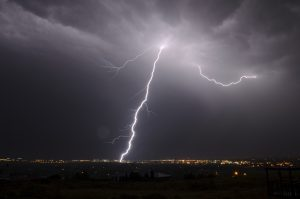 Stormy clouds shoot down a lighting bolt at the earth from the heavens.