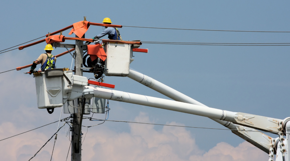 two construction workers in a boom truck working on electrical lines