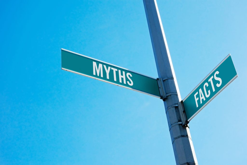Road sign symbolizing decision between Myths and facts