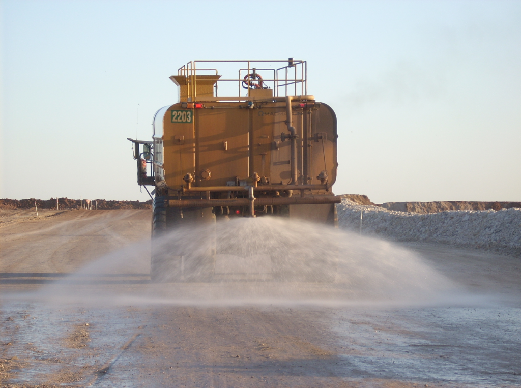 road haul truck spraying down dirt at an open pit mine