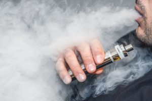 A man smokes an electronic cigarette on a gray background, blowing a stream of smoke. Copy space. Close up.