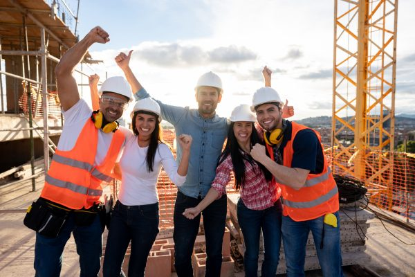 Group of construction workers looking very happy at a building site looking at the camera smiling with arms up