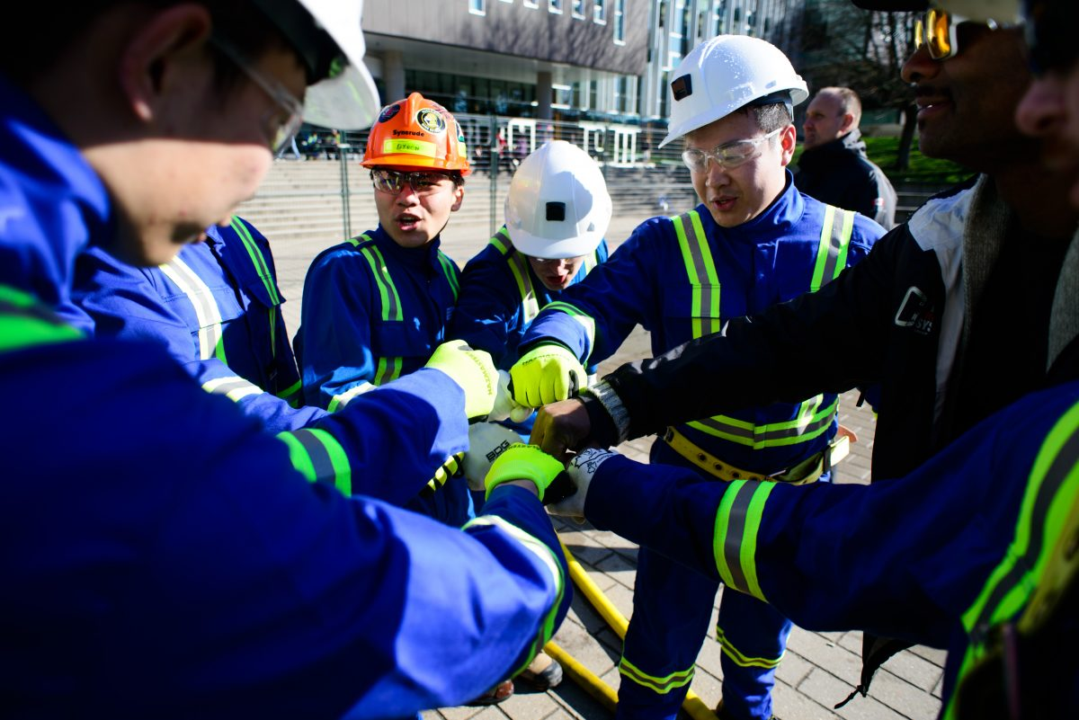 group of mining students fist bumping during the Canadian International Student Mine Rescue Competition