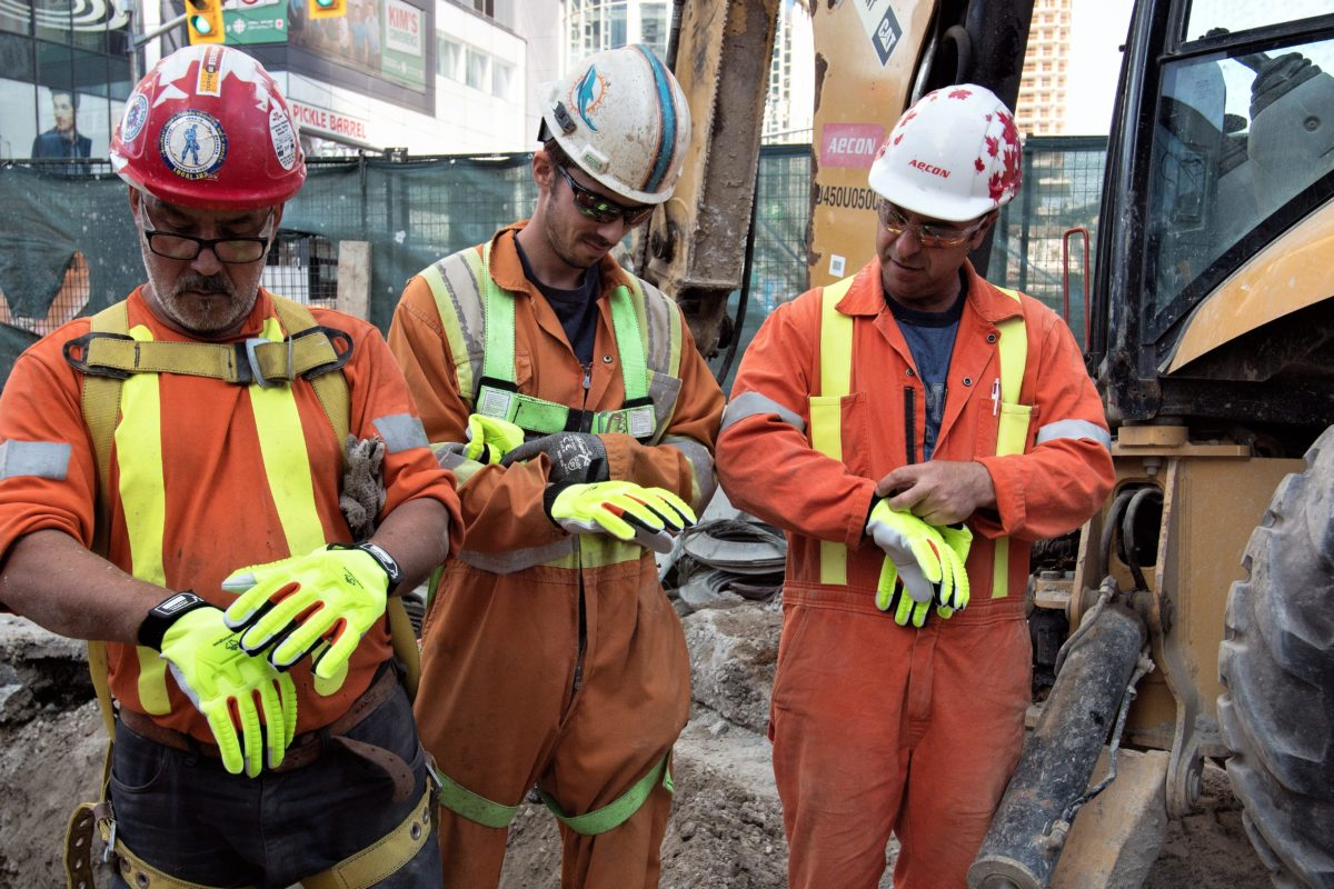 construction workers putting on gloves
