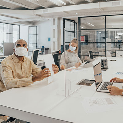 Image of man and woman wearing face mask and sitting in the office