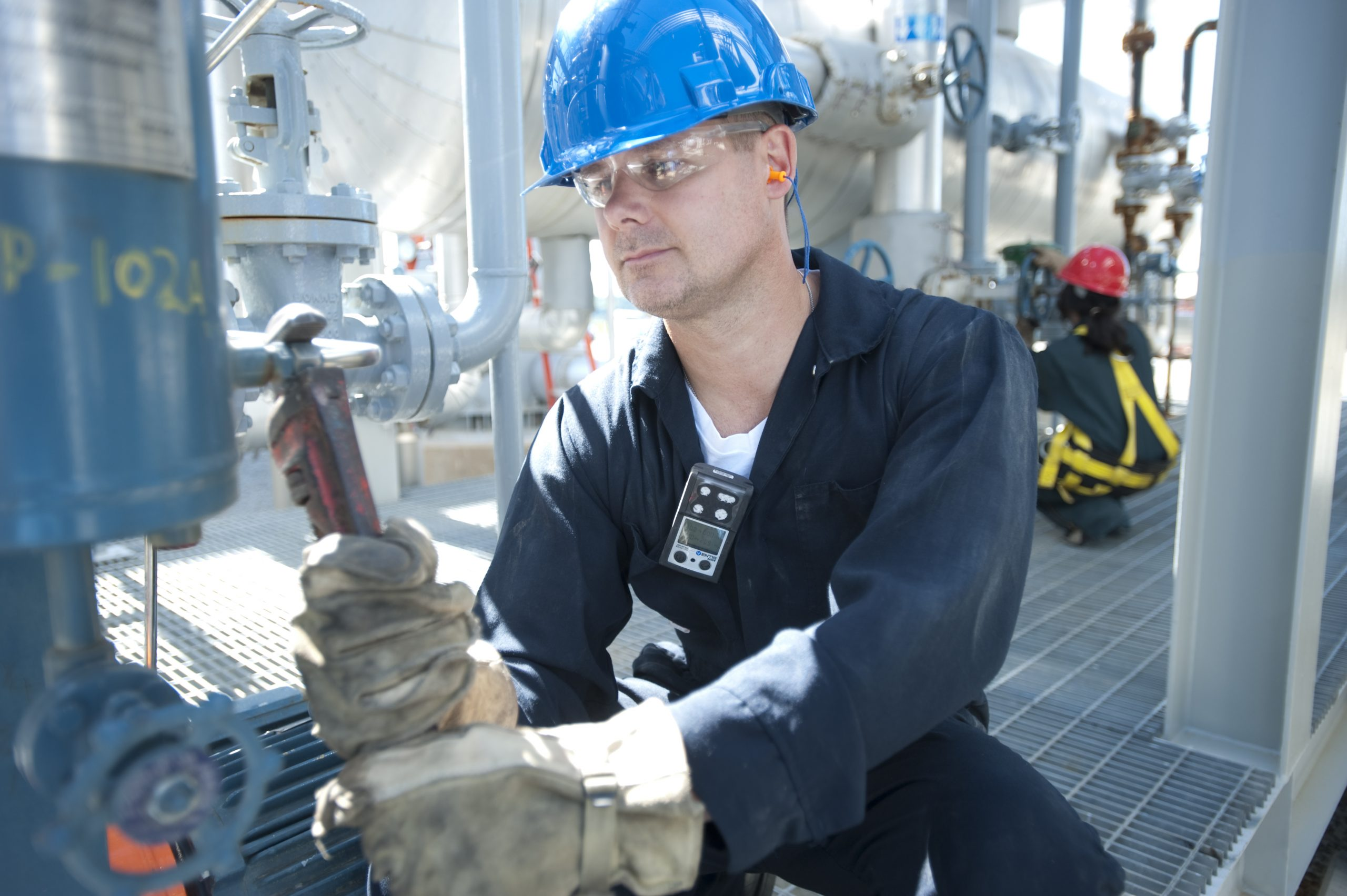 man wearing gas monitor and using a wrench to open a valve