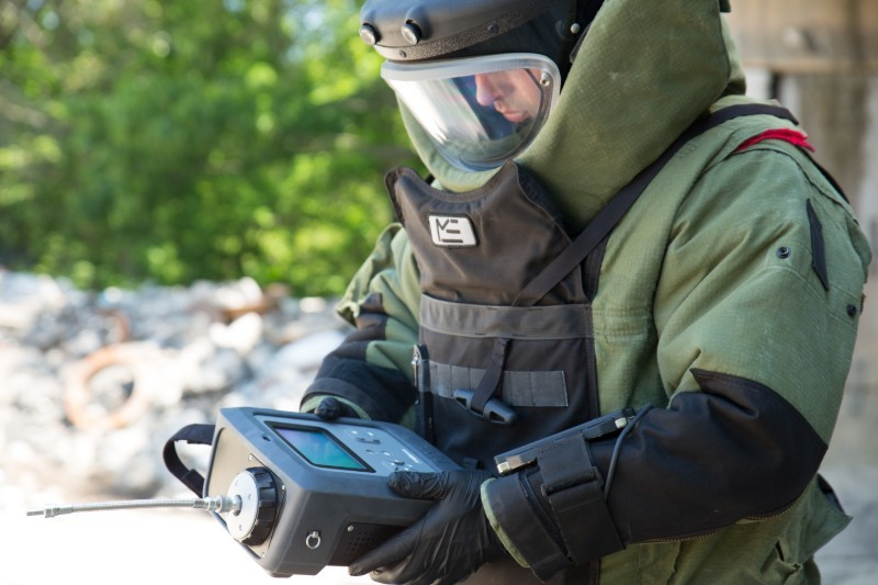 man wearing bomb suit holding an mx908