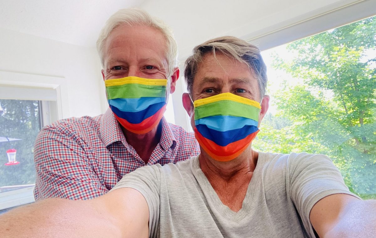 two people taking a selfie while wearing rainbow masks